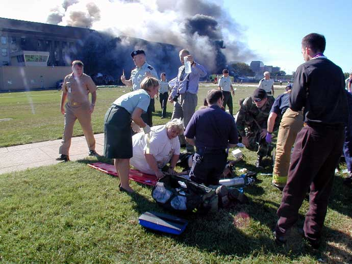 Color photograph showing medical personnel and volunteers working the first medical triage area set up outside the Pentagon after the attack.