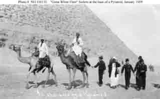 Sailors (wearing Fez hats) accompanied by local guides on camels at base of one of the Giza Pyramids during Egyptian sightseeing tour, January 1909.