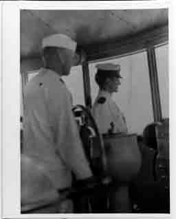 Lieutenant John E. Lewis (center), Officer of the Deck, standing watch in Connecticut's pilothouse.