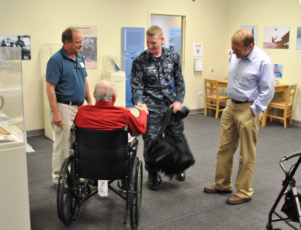 NMAS visitor in wheelchair shaking hands with sailor.