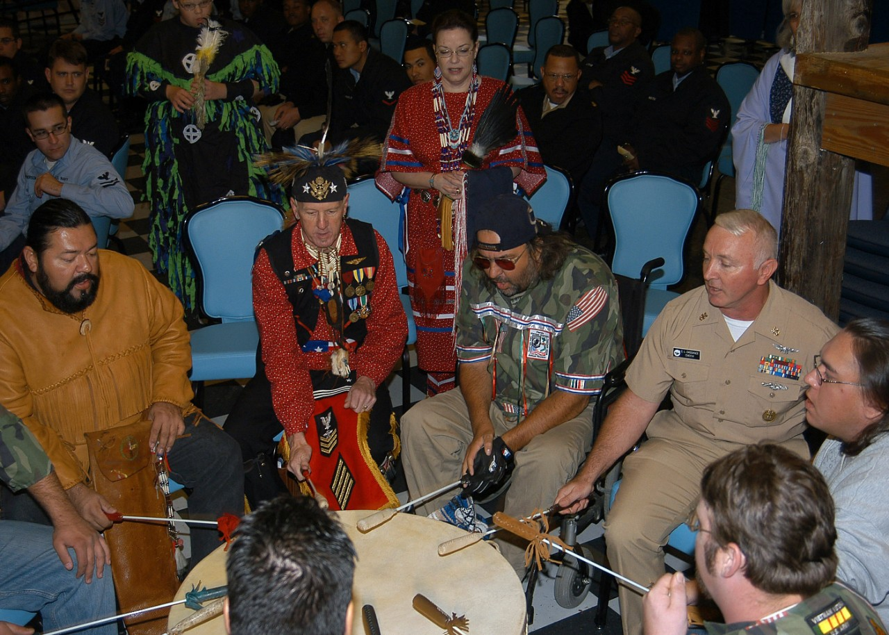 061121-N-6159N-001:  CMDCM Carl L. Dassance, November 2006.   USS John F. Kennedy's (CV-67) Command Master Chief, CMDCM Carl L. Dassance pounds on a ceremonial drum during the Native American and Alaskan Heritage celebration held November 21.  Dassance, who belongs to the Ojibwa tribe, is also a member of the Native American organization Family Drum, who acknowledge their heritage by playing their ceremonial drum weekly to honor Native Americans who serve in the armed forces.  This aircraft carrier was at Jacksonville, Florida.   Navy photo by Mass Communication Specialist Seaman Nathan L. Anderson.  Official U.S. Navy Photograph.