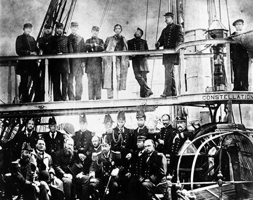 NH 91725:   USS Constellation (1855-1953), officers pose with welcoming officials at Cork, Ireland, upon her arrival with Irish relief supplies, 1880.   NHHC Photograph Collection.