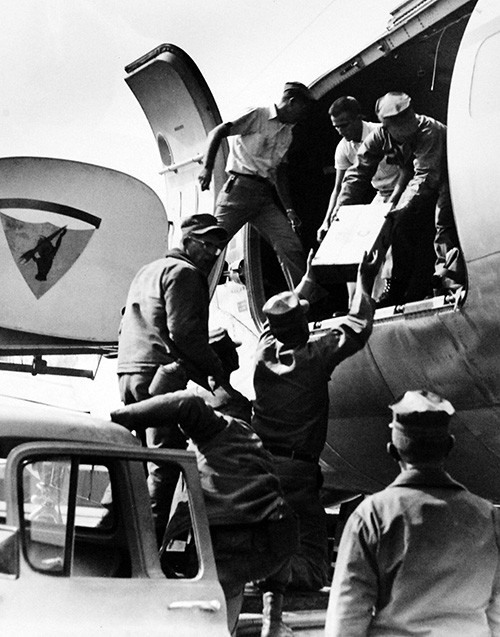 330-PSA-75-64 (USN 1093135):  U.S. Navy Seabees load their tools and equipment aboard aircraft at Point Mugu, California, as they prepare to depart for Alaska.  The group, consisting of 152 men from Mobile Construction Battalion Nine, is composed of electrical and utilities specialists.  They will help restore these essential services to parts of Alaska that suffered such severe damages in the recent earthquakes and tidal waves.  Other Navy planes have been carrying shipments of food, clothes, portable generators, heating units, and living supplies to the people of Alaska.  Photograph released March 31, 1964.  Official U.S. Navy Photograph, now in the collections of the National Archives.