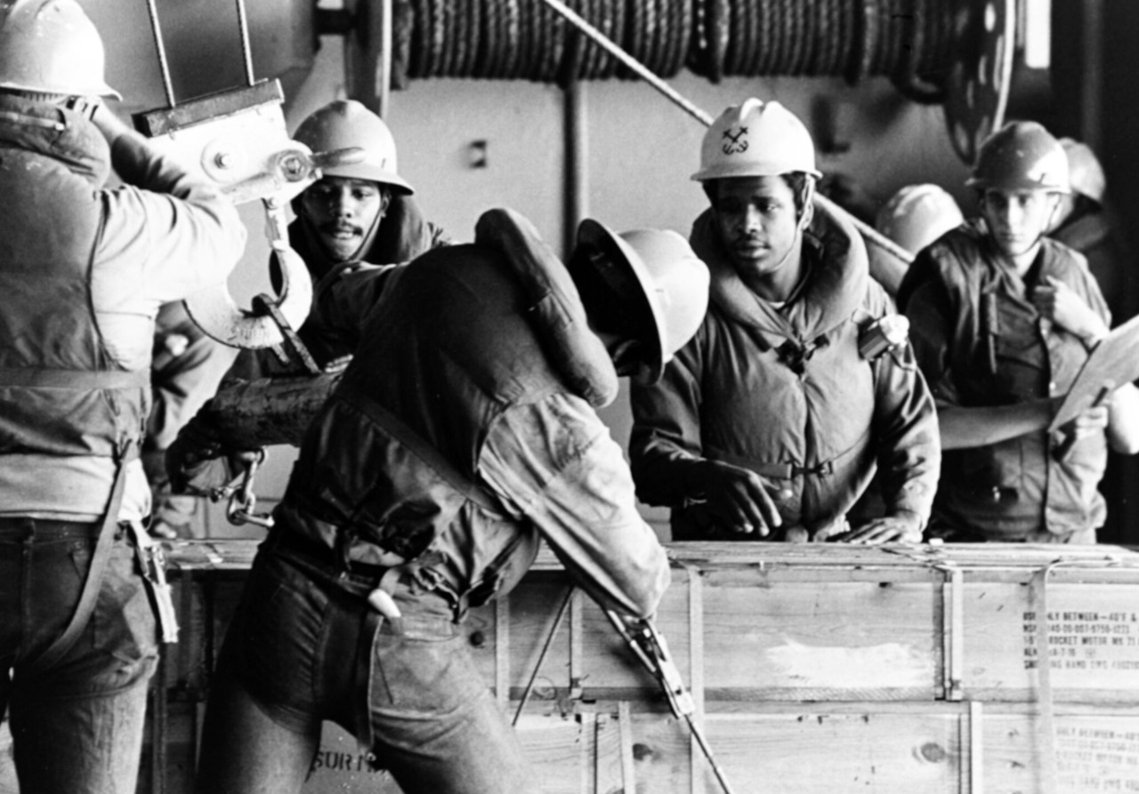 NH 97659:  USS Forrestal (CV-59).  Crewmen secure the cable and hook on a box, during underway replenishment operations in the Atlantic Ocean, 26 June 1976. Photographed by PH1 G. Burgess. Naval History and Heritage Command Photograph.