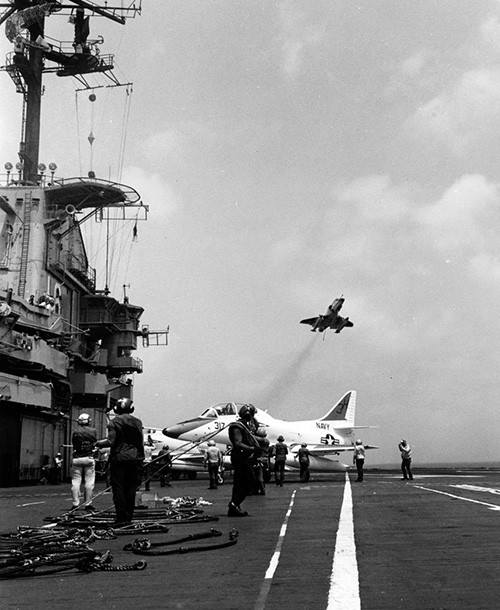 NH 97497:  USS Lexington (CVT/AVT-16), flight deck activity during the 1970s or 1980s).  A TA-4J Skyhawk is parked in the center as another passes overhead.   NHHC Photograph Collection.
