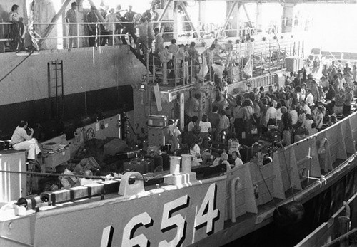 LCU 1654 unloads refugees from war-torn Lebanon in the well of the dock landing ship USS Spiegel Grove (LSD 32) as the ship stands off Beirut.  Spiegel Grove took 276 people to safety in Athens, Greece, during Operation Fluid Drive.   Photographed by PH1 A.J. Winguette, June 20, 1976.   NHHC Photograph Collection, Navy Subject Files, Wars and Events.