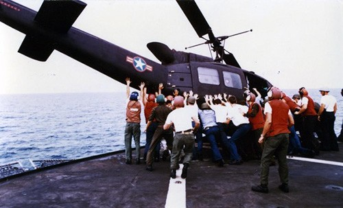 Operation Frequent Wind, April 29, 1975   A Vietnamese Air Force HU-1 Huey Helicopter is deliberately ditched near USS Blue Ridge (LCC-19), as one of the ship's boats stands by to pick up the pilot.   This helicopter was one of 15 which landed on board USS Blue Ridge with Vietnamese military personnel and families during the evacuation.   The helicopters had to be pushed or ditched into the sea because of the lack of space on deck.  NHHC Photograph Collection, Navy Subject Files.