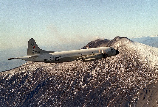 "330-CFD-DN-SC-88-08331:   An air-to-air right side view of a P-3 ""Orion"" aircraft from Patrol Squadron 49 (VP-49) flying past Mount Etna while returning from a submarine tracking mission. The squadron, based in Jacksonville, Fla., is deployed to Sicily, August 1, 1985.   Official U.S. Navy photograph, now in the collections of the National Archives."