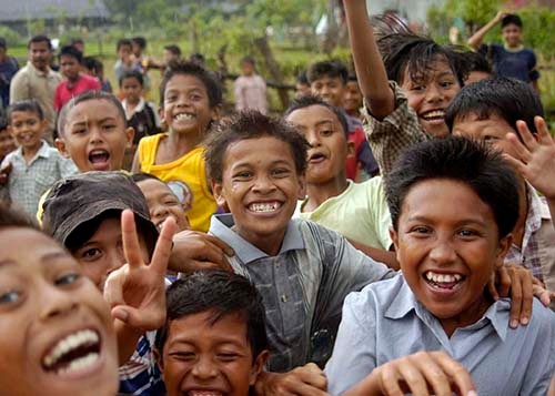 050105-N-5376G-019:   Island of Sumatra, Indonesia.  Indonesian children smile and cheer as U.S. Navy helicopters from USS Abraham Lincoln (CVN-72) fly-in purified water and relief supplies to a small village on the island of Sumatra, Indonesia.   Photographed by Photographer's Mate 3rd Class Benjamin D. Glass.   Official U.S. Navy photograph.