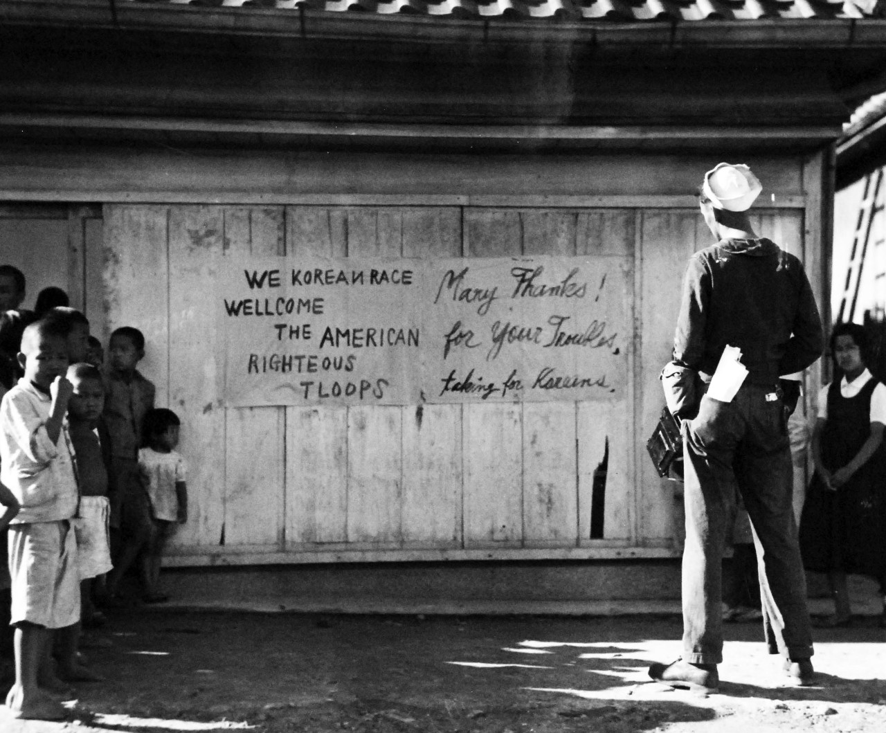 80-G-490500:   Occupation of Korea, September 8, 1945.   A U.S.Navy enlisted man stops to read a welcome sign an hour after the initial wave of the 24th U.S .Army Corps troops was landed at Jinsen, Korea, by Vice Admiral D.E. Barbey's Seventh Amphibious Force, 8 September 1945.   Official U.S. Navy Photograph, now in the collections of the National Archives.