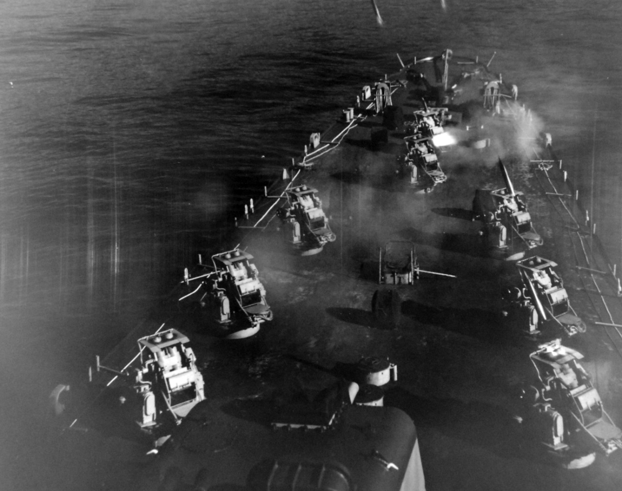 80-G-689755:  USS Carronade (IFS-1), 1955-59.  Firing rockets from deck.   Carronade was an Inshore Fire Support Ship, built to provide gunfire support to amphibious landings or operations close to shore. Official U.S. Navy Photograph, now in the collections of the National Archives.  (2017/11/01).  Photograph is extremely curved.