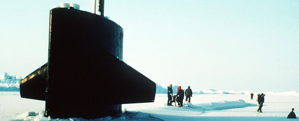 330-CFD-DN-ST-87-02290: USS Trepang (SSN-674), 1985.  The sail of the nuclear-powered submarine USS Trepang (SSN-674) protrudes from the ice near Ice Camp Opal, one of three research stations established on the polar ice cap during the Arctic Research and Environmental Acoustic (AREA) program. Area '85 is a Navy-sponsored expedition to study oceanography, acoustics, geophysics, communications and submarine warfare in the polar environment. Crew members are removing ice from one of the ship's hatches, July 5,1985. Photographed by JOC Fred J. Klinkenberger, USN.    Official U.S. Navy Photograph, now in the collections of the National Archives.