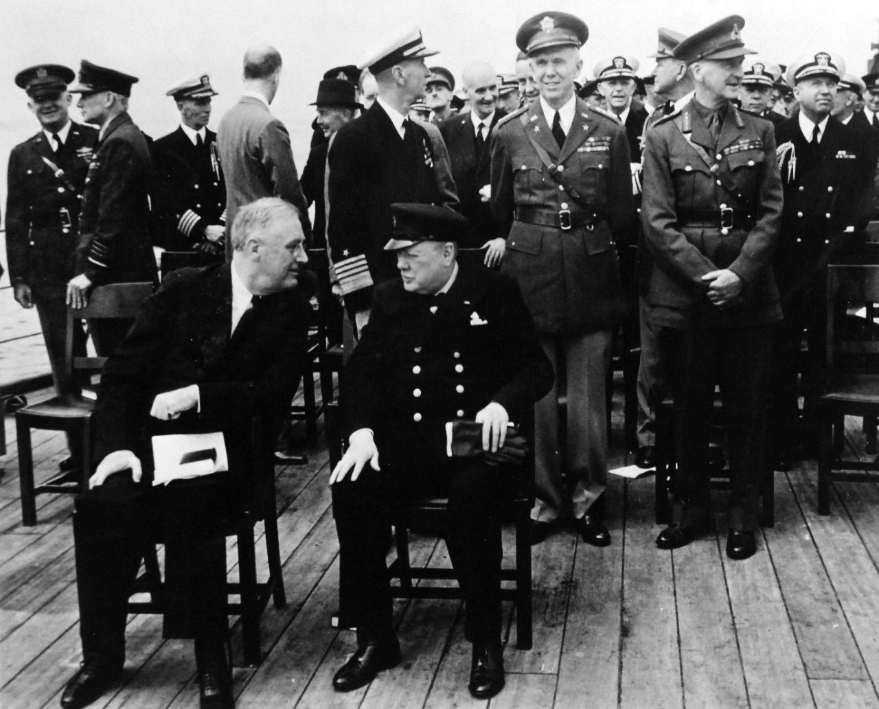 80-G-26863: Atlantic Charter, August 1941.  Informal group photograph including President Franklin D. Roosevelt and Prime Minister Winston S. Churchill on deck of HMS Prince of Wales following church services during the Atlantic Charter.  Photograph released August 1941.   Official U.S. Navy Photograph, now in the collections of the National Archives.  (2016/03/22).