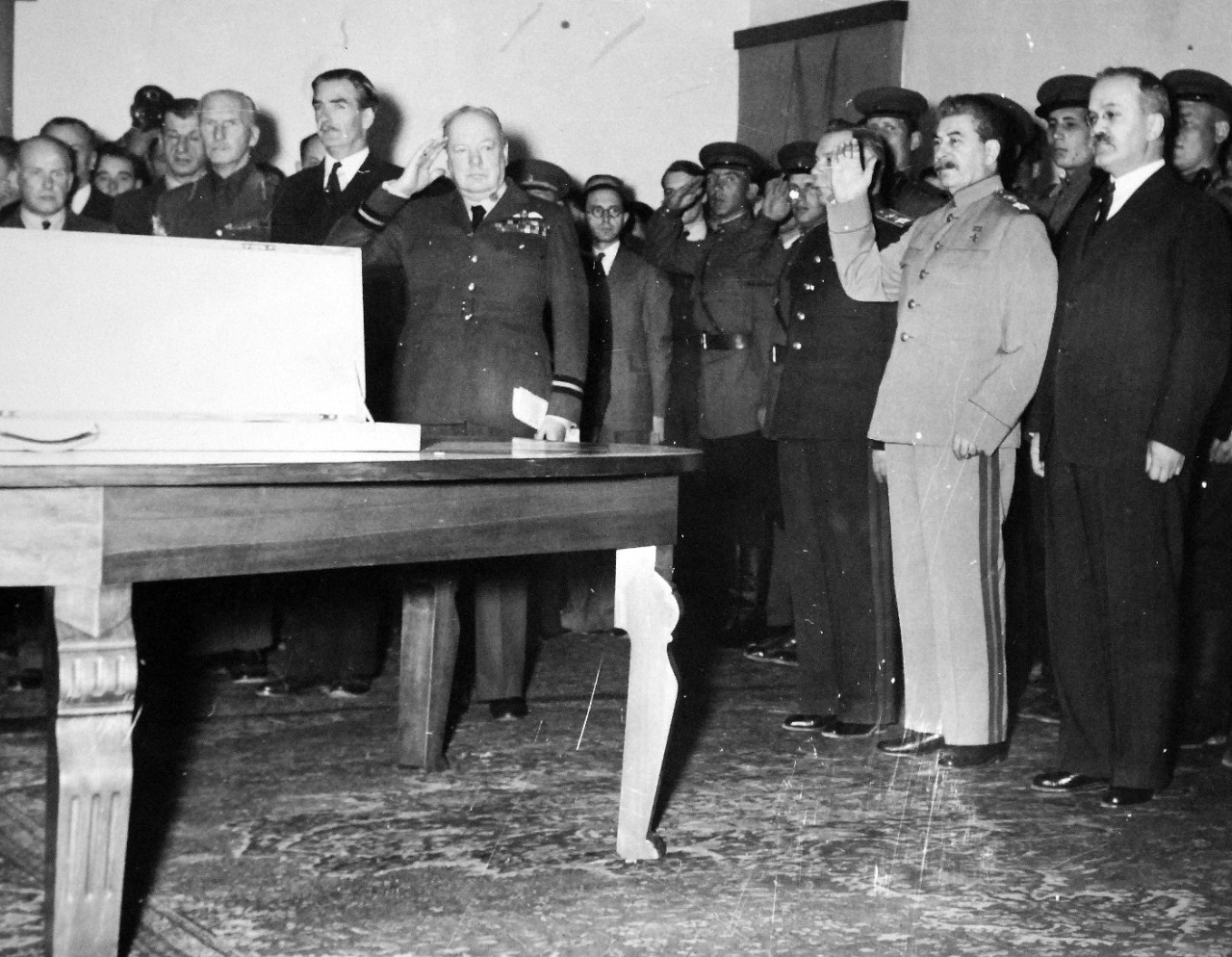 Lot 11597-4:  Tehran Conference, November-December 1943.   The presentation of the Stalingrad sword in the reception room of the Russian embassy.  Prime Minister Winston Churchill and Marshal Josef Stalin, hand upraised, during the playing of the Russian national anthem.  Anthony Eden is behind the Prime Minister; Stalin is flanked by General Voroshilov (right) and Foreign Minister Molotov, (left).  The sword was presented to the people of Stalingrad as a token of the regard and admiration of the British people for the gallant defense of the city. Note, V. M. Molotov, Peoples' Commissar for Foreign Affairs, to Stalin's right.  U.S. Army photograph from the collection of the Office of War Information.  Courtesy of the Library of Congress.    (2016/01/15).