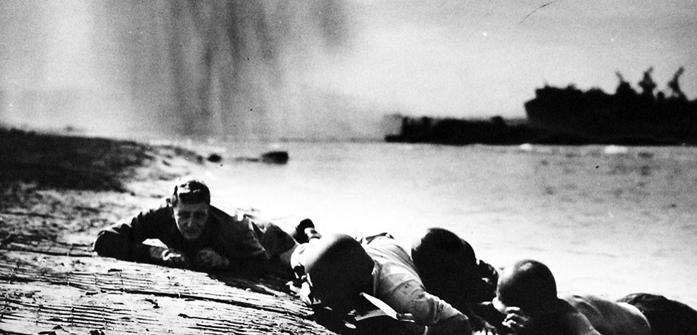 Image: Lot-916-12:   Underneath Dropping Bombs.  U.S. Coast Guardsmen and Navy beach battalion men are shown hugging the shaking beach at Paestum, just south of Salerno, as a German bomber unloads on them.  U.S. Coast Guard Image:  26-G-2000.  Courtesy of the Library of Congress.  (2016/05/19).