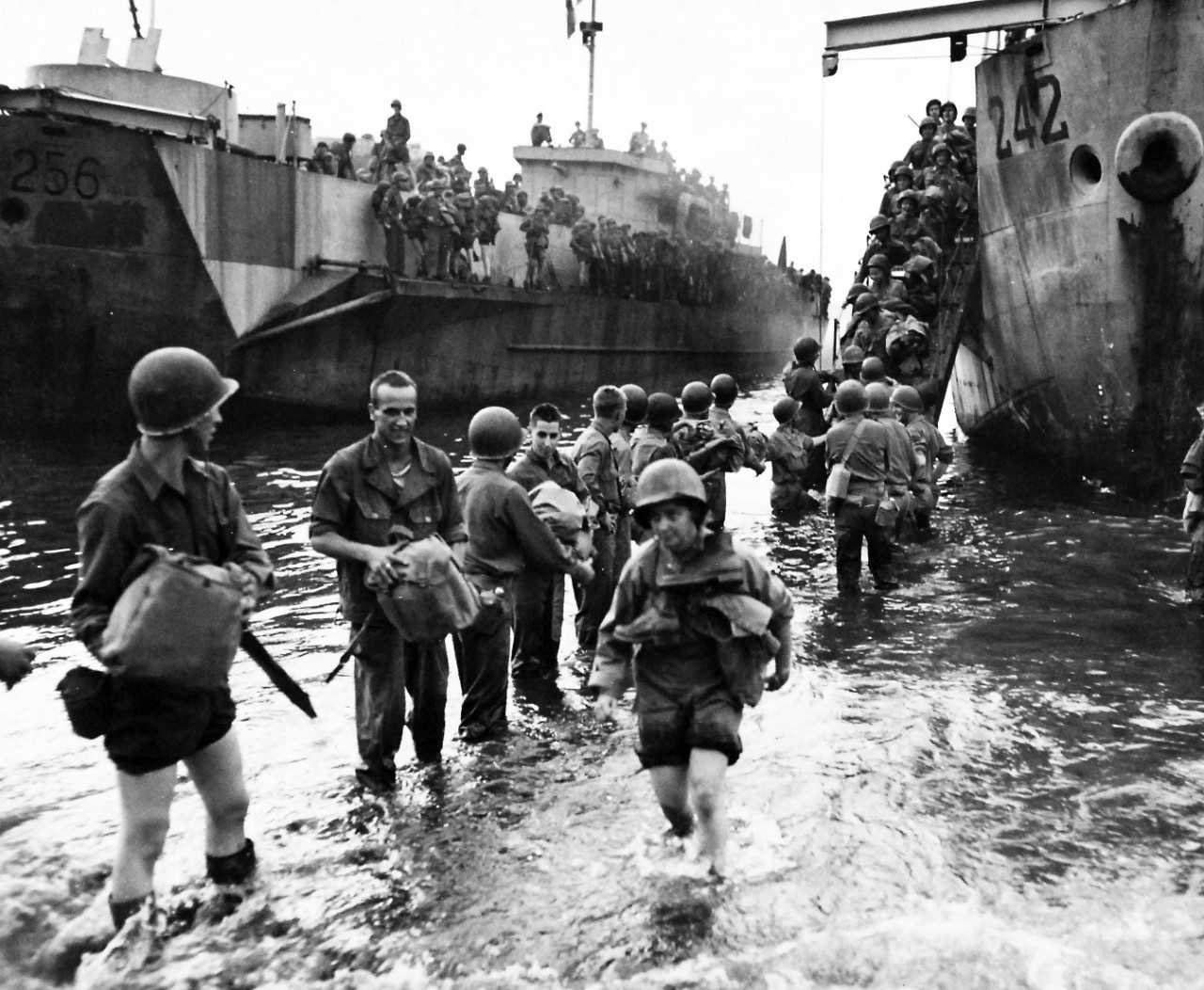 80-G-54371:   Naples, Italy, November 1943.   U.S. Army nurses and soldiers at Naples, Italy, wading ashore from LCI-242.   The nurse in the foreground carries her boots around her neck for safekeeping.   Photograph released November 4, 1943.  U.S. Navy photograph, now in the collections of the National Archives.  (2016/06/28).
