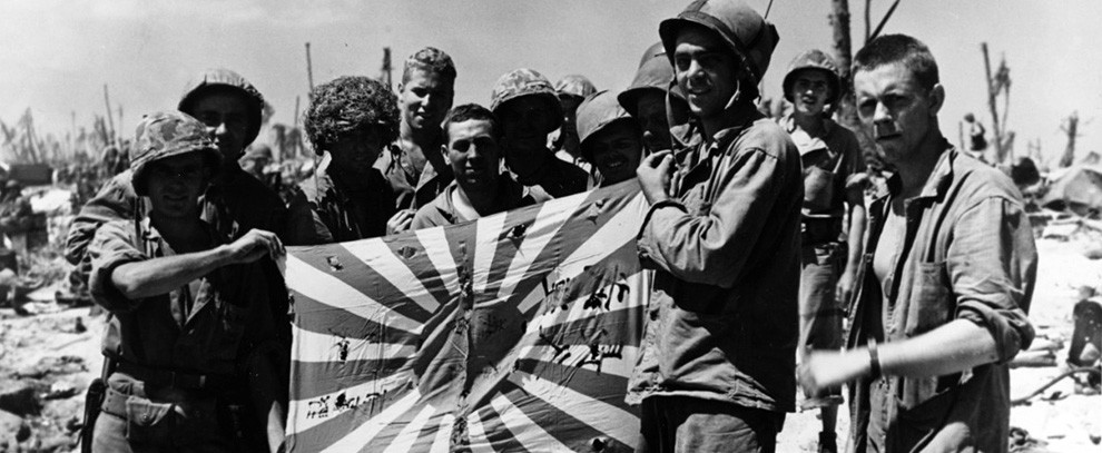 80-G-216033:  Operation Catchpole, February 1944. U.S. Marines and Coast Guardsmen proudly display a Japanese flag on Engebi Island, February 19, 1944.   Official U.S. Coast Guard Photograph, now in the collections of the National Archives.