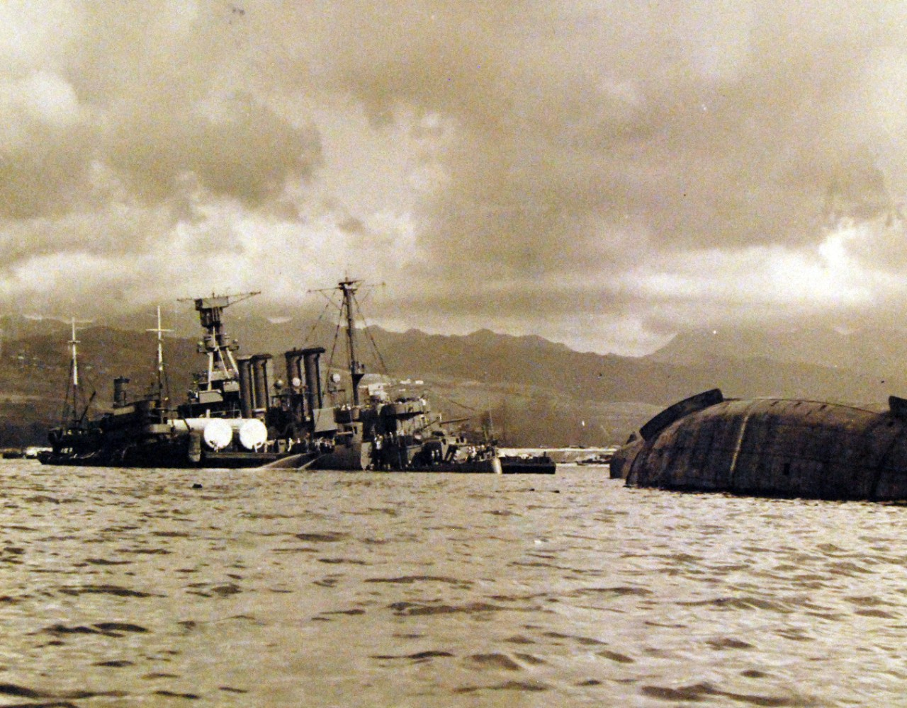 80-G-32742:   Japanese Attack on Pearl Harbor, December 7, 1941.   The capsized USS Utah (AG 16) and USS Raleigh (CL 7) are shown after the attack. Official U.S. Navy photograph, now in the collections of the National Archives. (9/9/2015).