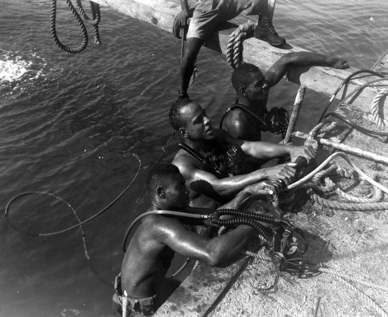 "Seabee install submarine POL pipeline off White Beach, Tinian, 1944. 55-gallon drums were used to keep the pipeline afloat to the ""gas station"" located offshore."