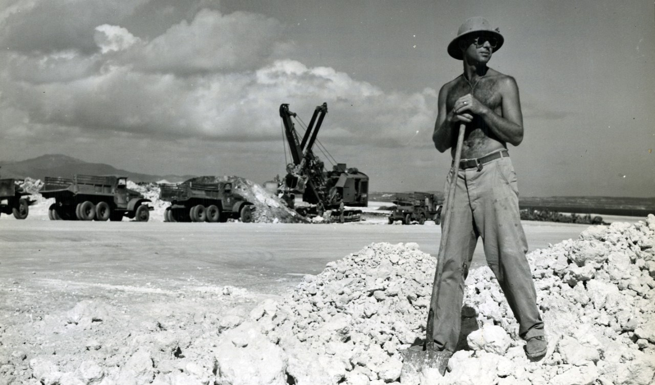 Seabee Vance Shoemate directs truckers unloading coral for runways. The truckers drive at 45 mph. In the background is a fleet of trucks awaiting their turn for leads from the scoop shovel. Working on B-29 bomber base on Tinian.