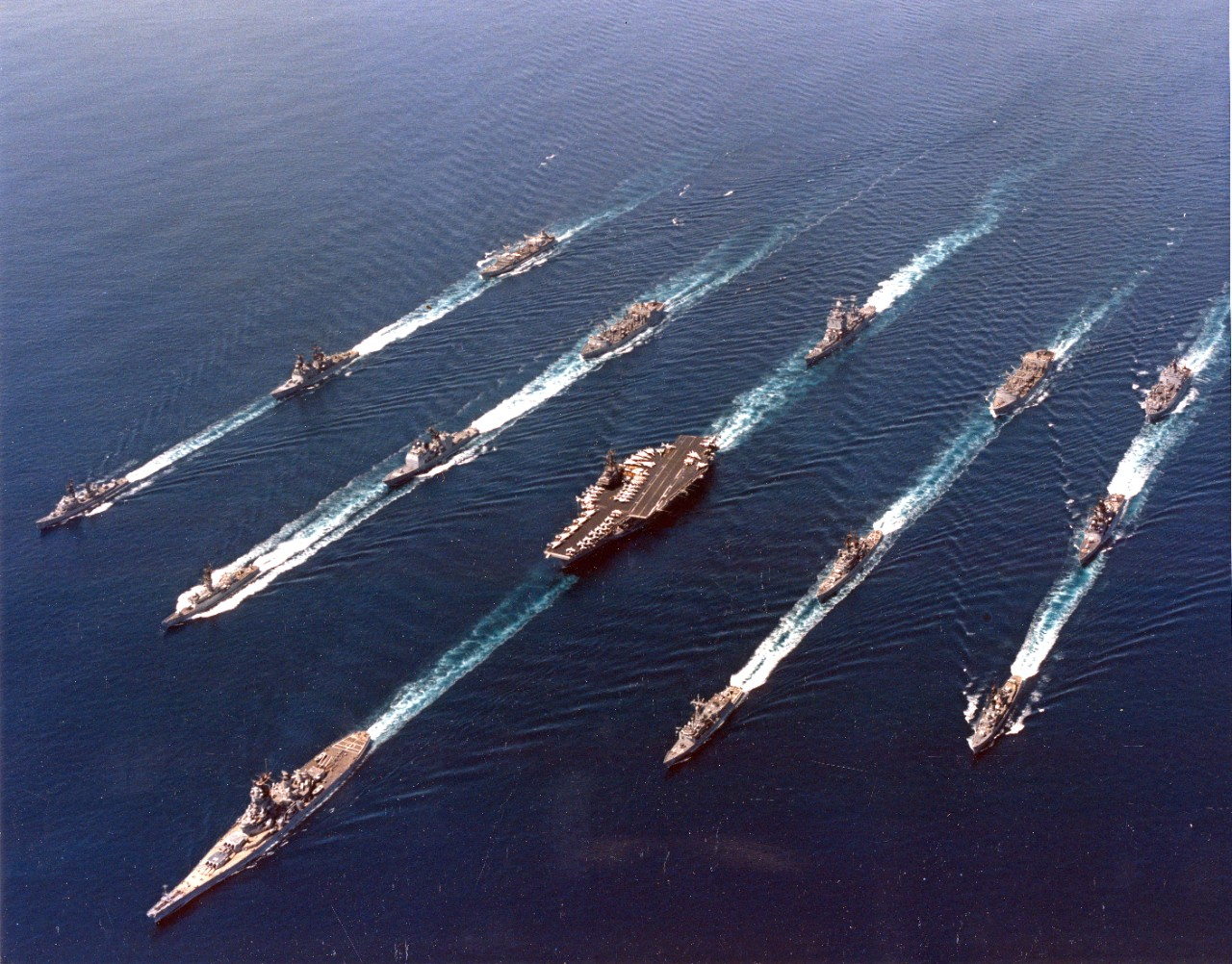 An Iowa class battleship leads a battle group at sea in the 1980s.