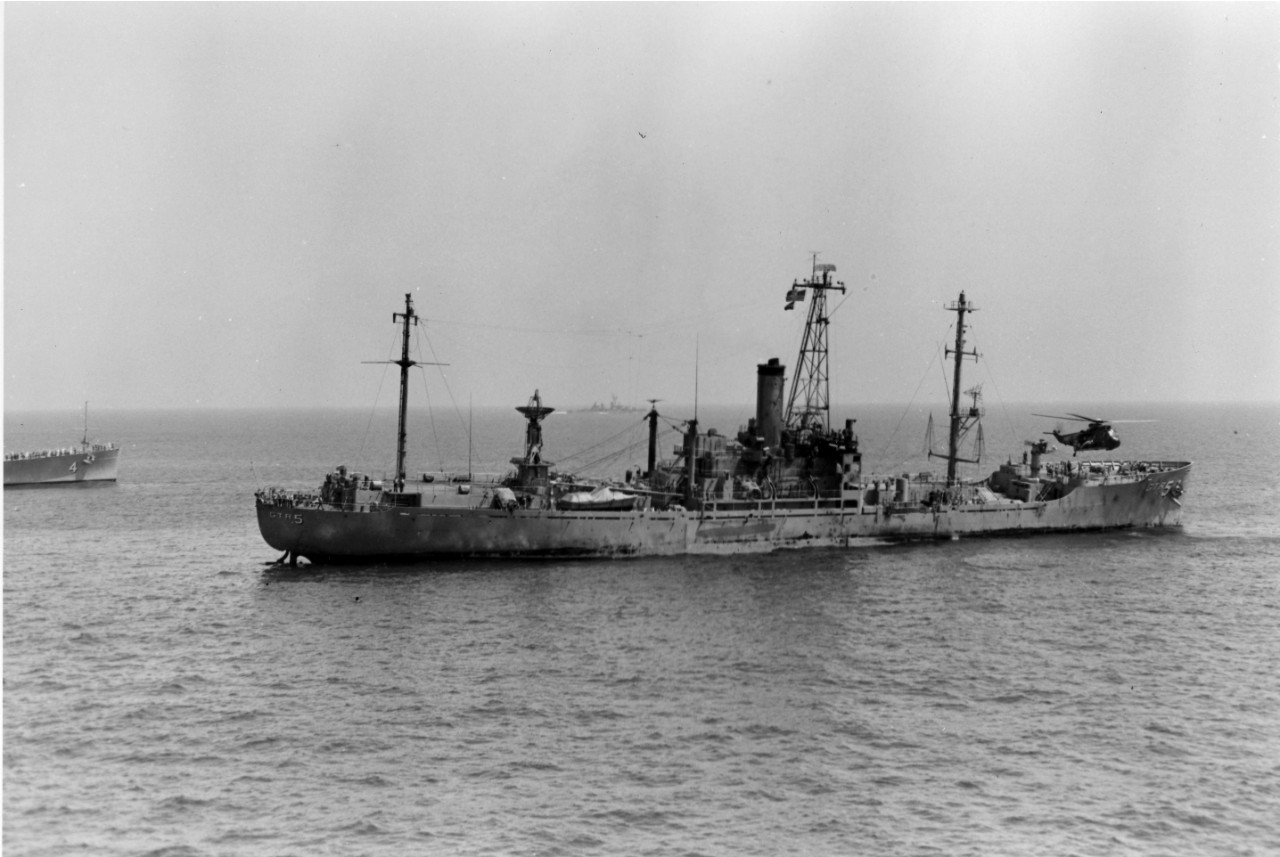 With a decided starboard list, the USS Liberty (AGTR-5), accompanied by the guided missile cruiser USS Little Rock (CLG-4), limps slowly toward the Port of Valletta, Malta, for repairs following the attack by Israeli torpedo and aircraft. The helicopter hovering over the bow of the ship is removing the wounded and dead to the attack carrier USS America (CVA-66).