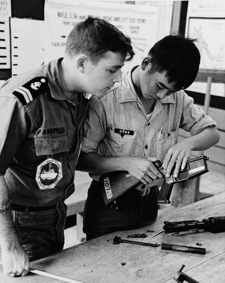 An instructor watches closely as a Vietnamese Student assembles a M-16 rifle