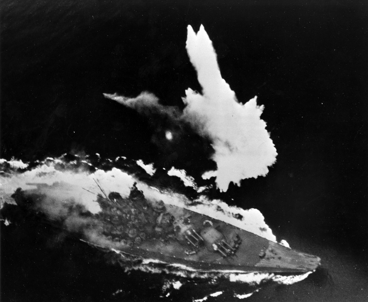 Yamato maneuvers frantically under attack as a bomb explodes off its port side. The fire in the area of the 6.1 inch turret can be clearly seen.