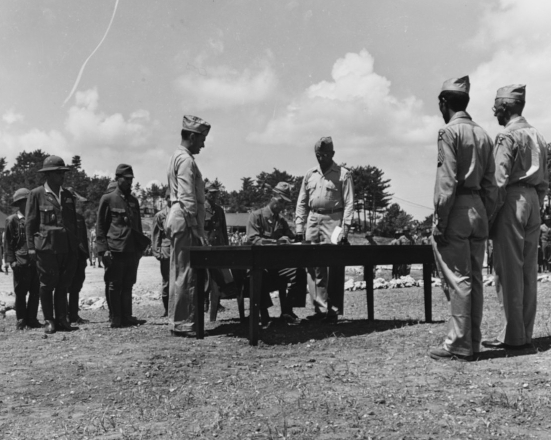 A Japanese offcer signs the surrender document on Okinawa, 7 September 1945. Also at table, standing (left to right) are Col. Phillip Bethune and Maj. Gen. Frank Merrill. At right is also General Joseph Stillwell (80-G-344922).