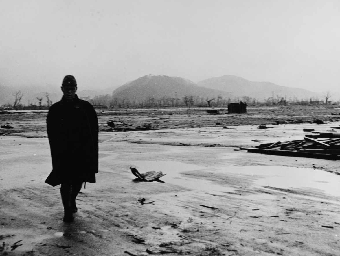 Black-and-white photograph of a Japanese soldier walking toward the viewer, silhouetted against a background that shows the flattened city of Hiroshima and scattered debris. In the distant background are burnt trees and mountains.