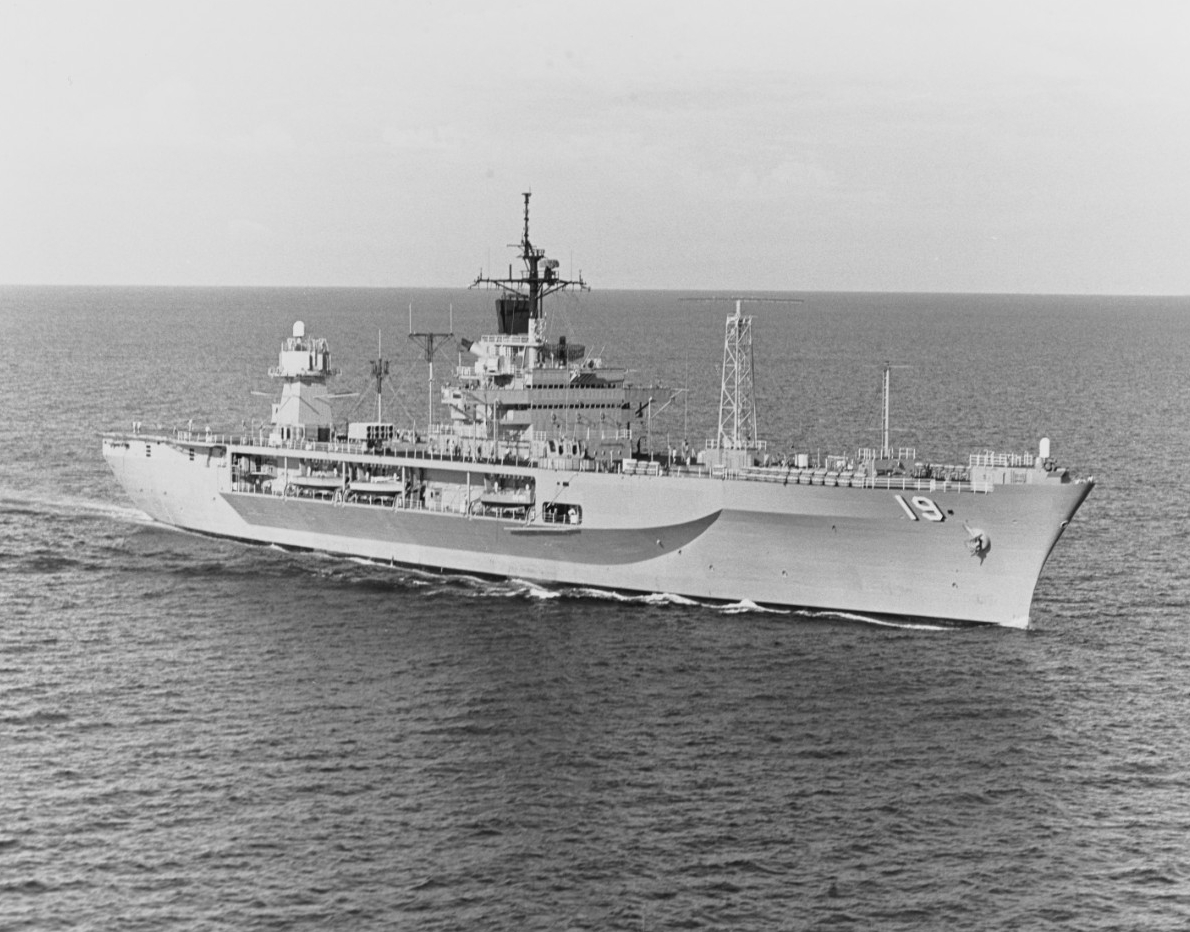 Black-and-white photograph of USS Blue Ridge (LLC-19) steaming forward, bow to the right, on opean ocean. The ship's hull number, 19, is clearly visible on the port side.