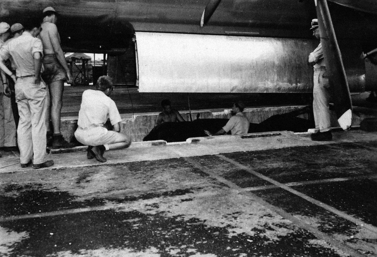 77-BT-130:   Tinian Island, August 1945.  Side shot of unit in pit, being lined up to hoist Little Boy into bomb bay; canvas cover is still on unit.  Lieutenant Wright in pit and Commander A.F. Birch on edge of pit, directing operations.  Official photograph of the Office of Chief of Engineers, now in the collection of the National Achives.   (2015/08/25).