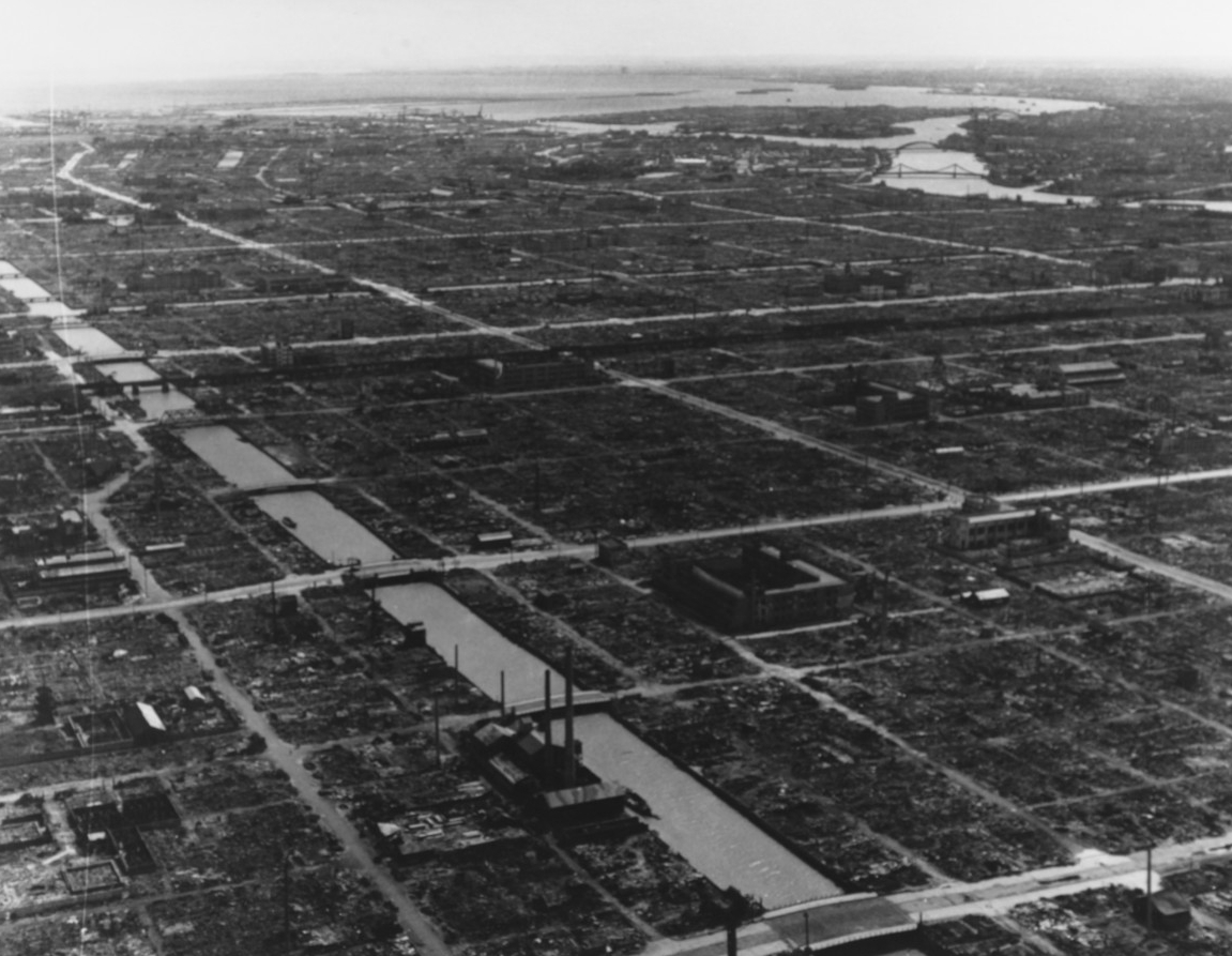 Black-and-white aerial photograph of a flattened city, Tokyo, but with canals and streets already cleared.