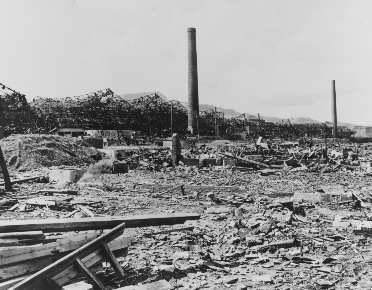 A ground-level view of damage to what appears to have been an industrial site in Nagasaki, Japan. The ground is littered with debris, with planks of wood in the lower left. In the background stands a series of ruins and two smokestacks, still standing.