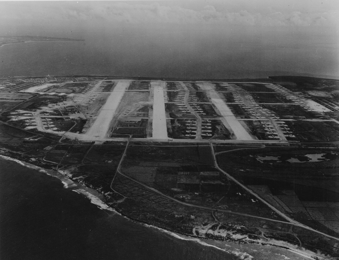 Black-and-white aerial photograph of Tinian, showing rows and rows of parked aircraft, which the caption identifies as B-29s belonging to the U.S. Army Air Force.