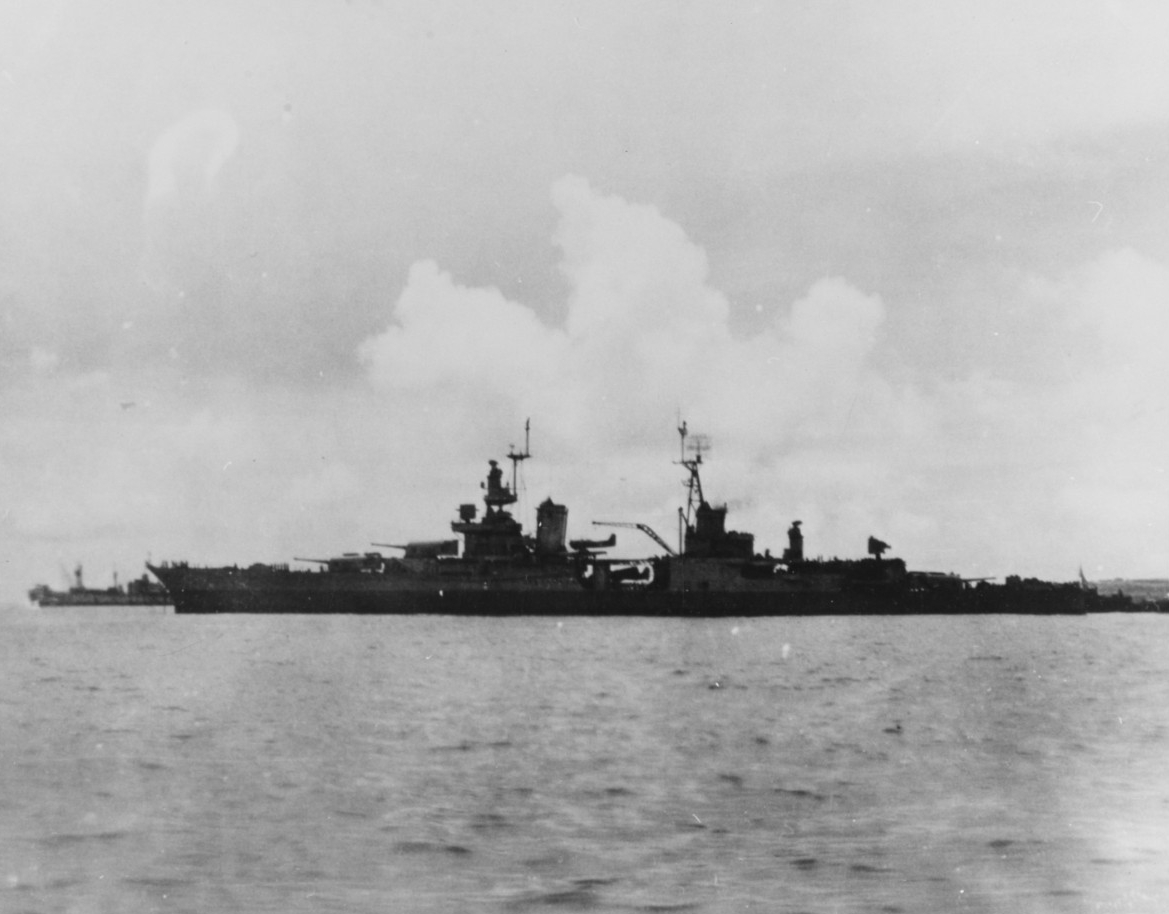 Black-and-white photograph seen from the side, backlit, with clouds, another ship, and land in the background.