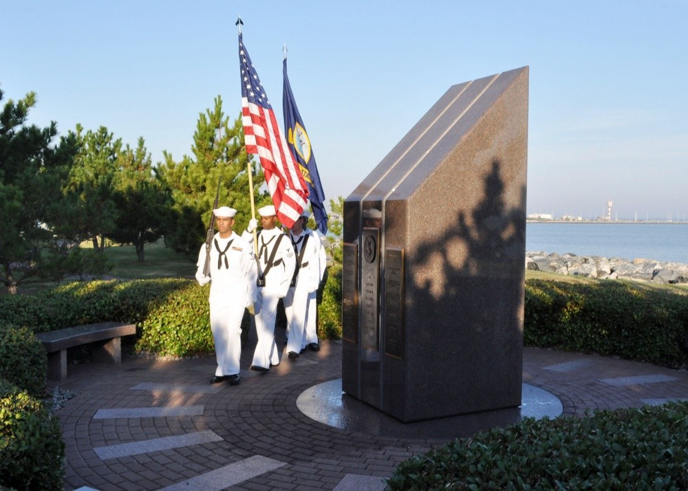 Members of a Navy honor guard from the guided-missile destroyer USS Cole practice rendering colors before a memorial service at the USS Cole Memorial at Naval Station Norfolk.