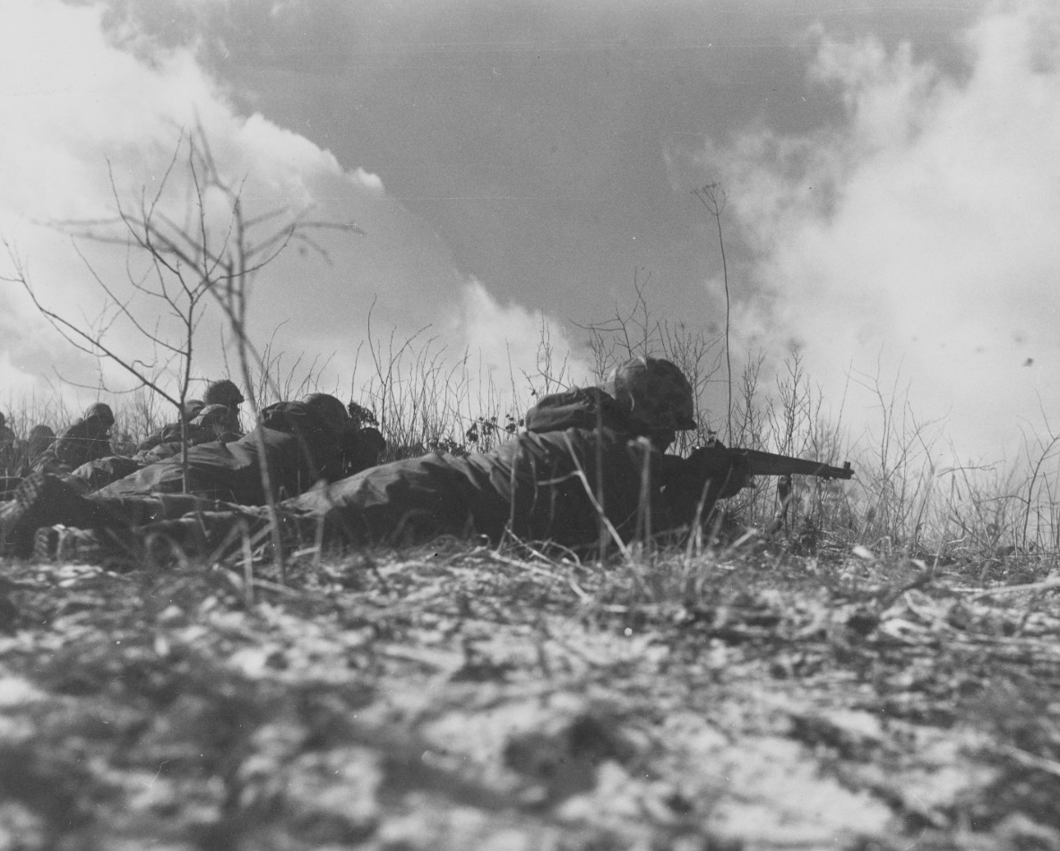 Marines lying on ground with guns