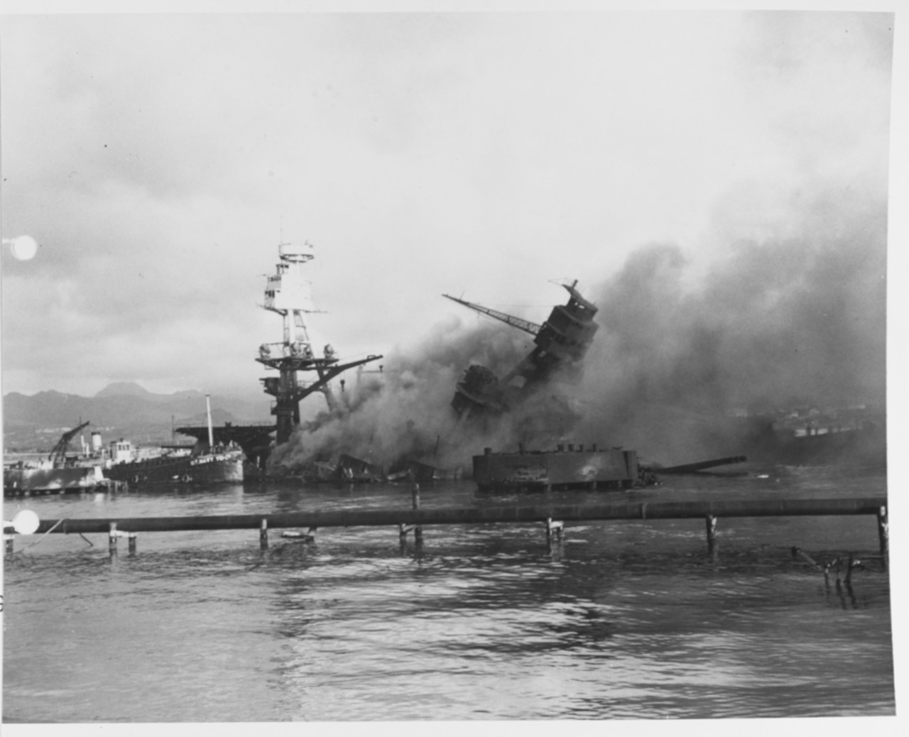 USS Arizona (BB-39) sunk and burning at Pearl Harbor, Hawaii, on 7 December 1941, after her forward magazines exploded when she was hit by Japanese bombs. YG-21 is alongside, helping to fight the fires. (NH 83062)