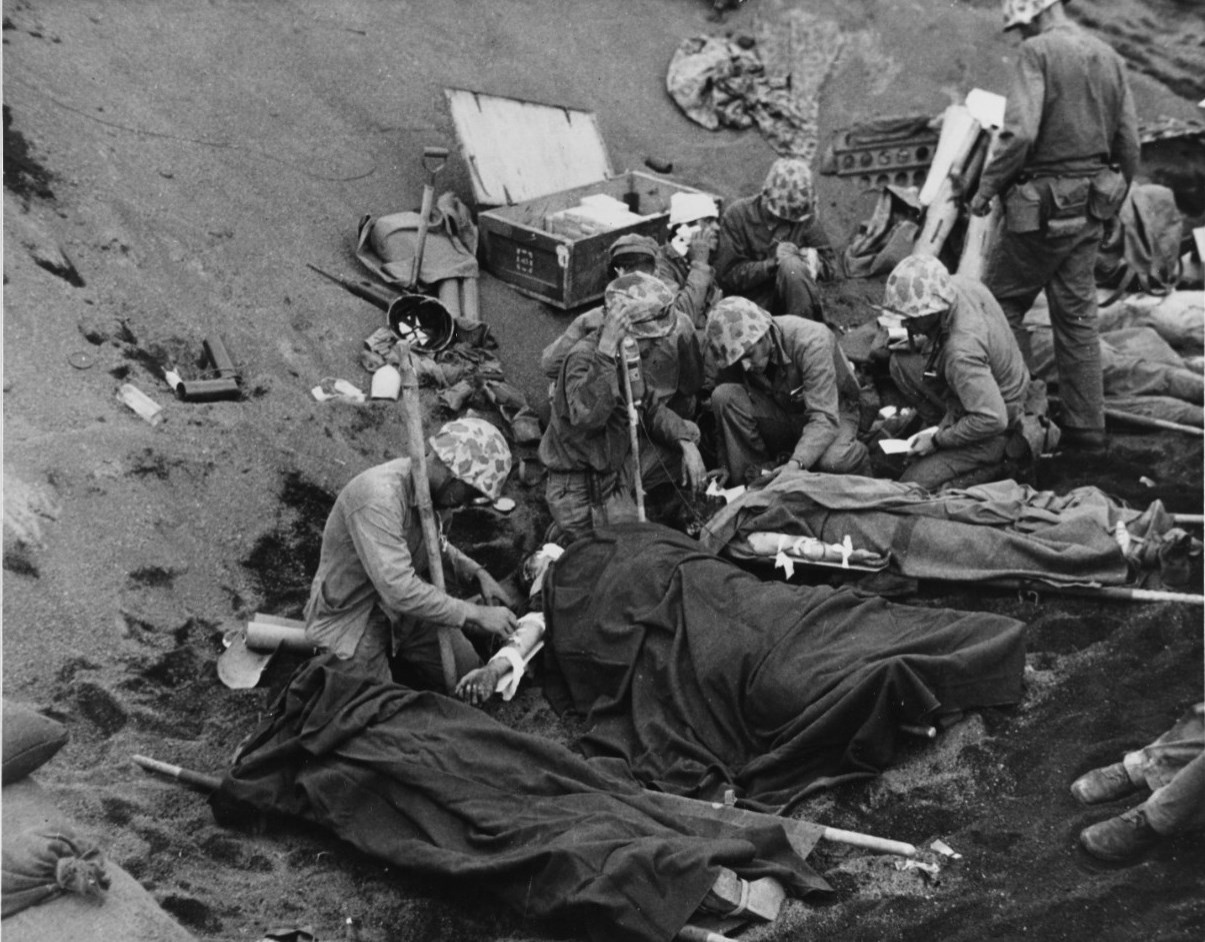 Iwo Jima Operation, 1945 U.S. Navy doctors and corpsmen administer to wounded Marines at an Iwo Jima first aid station, 20 February 1945. Navy Chaplain Lieutenant (Junior Grade) John H. Galbreath (right center) is kneeling beside a man who has severe flash burns, received in an artillery battery fifty yards or so away.