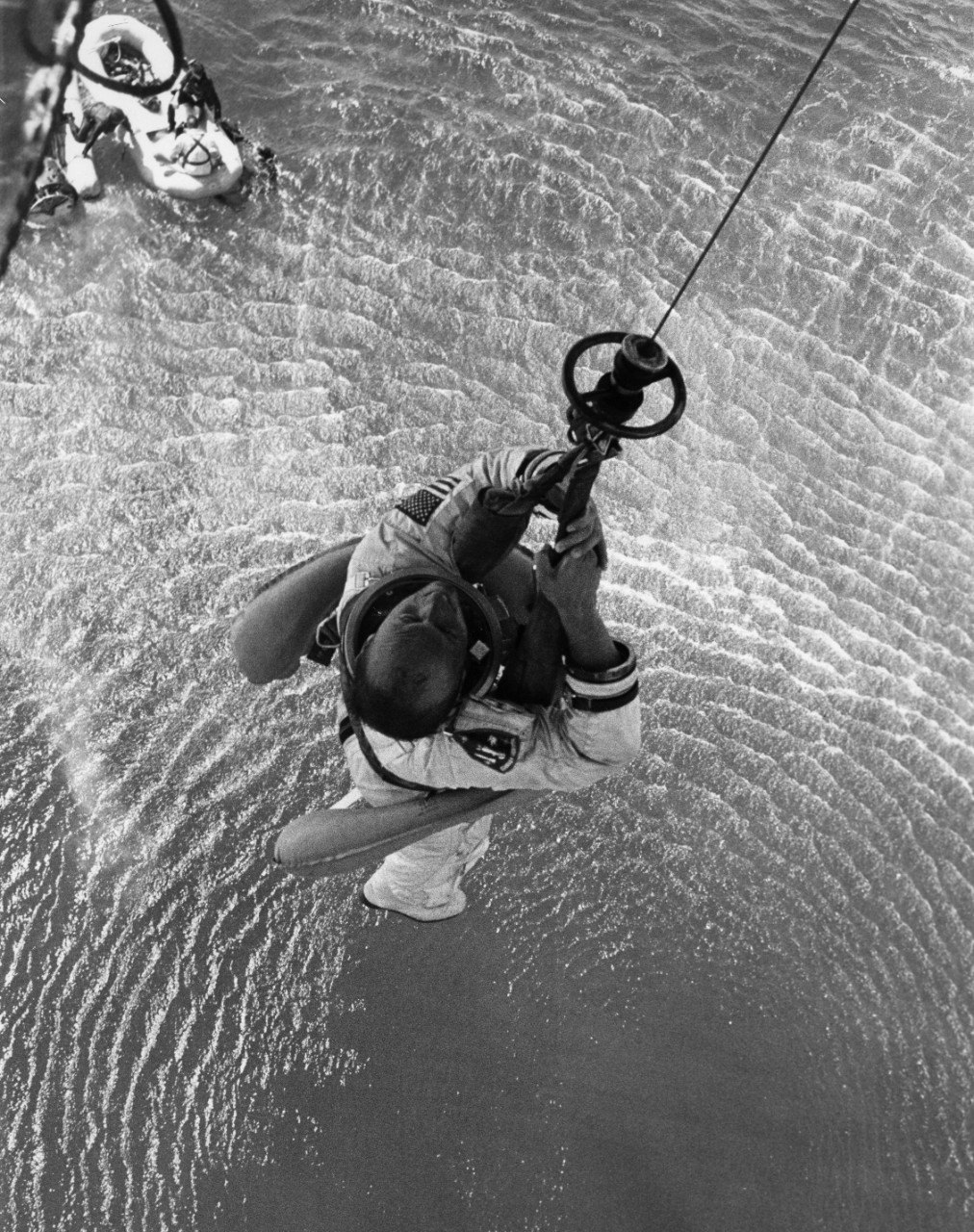 Gemini 11 astronaut Charles Conrad is hoisted aboard a recovery helicopter, with astronaut Richard Gordon in the raft below.