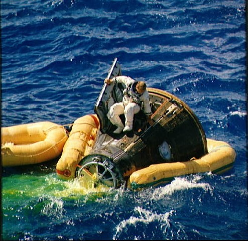 Astronaut Charles Conrad climbs from spacecraft after splashdown