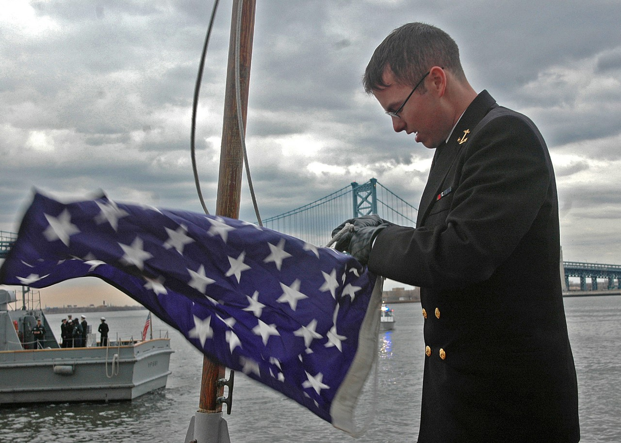 Midshipman 4th Class Nicholas D. Brockert raises the Union Jack aboard Yard Patrol Craft 691 (YP-691).