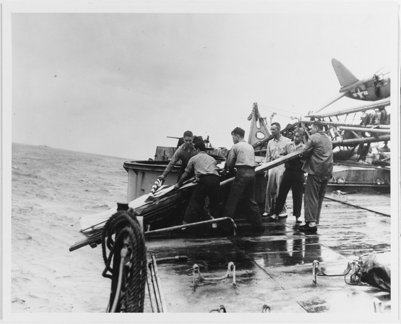 Burial at sea for crewmen killed when the ship was torpedoed off Formosa on 14 October 1944. Photographed while Houston was under tow on 15 October.