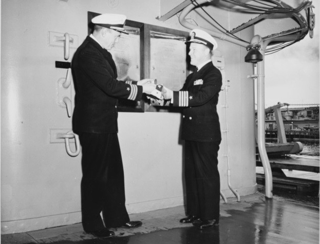 USS Baltimore (CA-68) commanding officer, Captain Scarritt Adams (right), receiving her commissioning pennant from his executive officer, Commander G.M. Boyd, following her final decommissioning ceremonies.