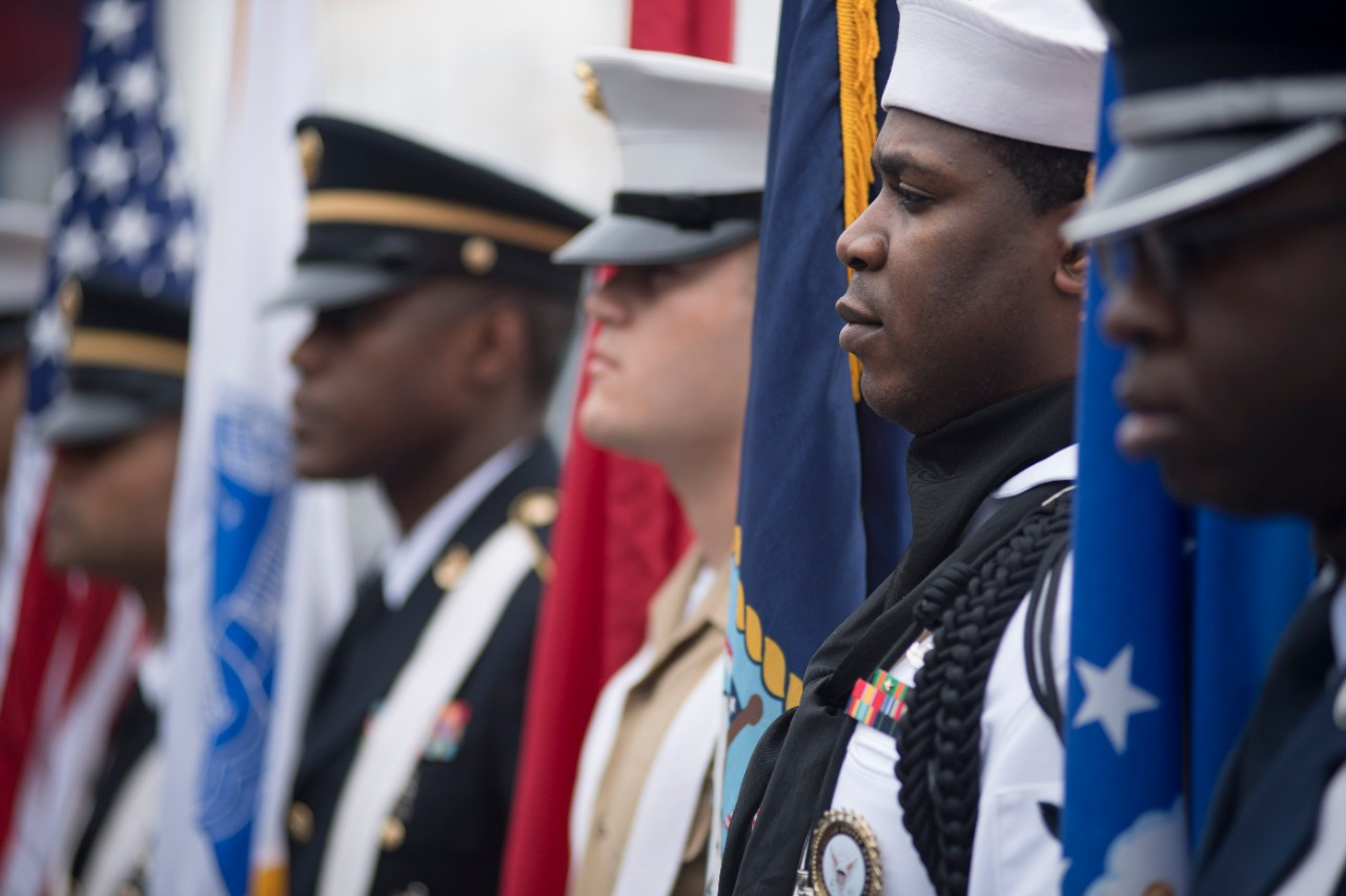 Members of a joint-service color guard stand by during a Memorial Day ceremony at the Intrepid Sea,