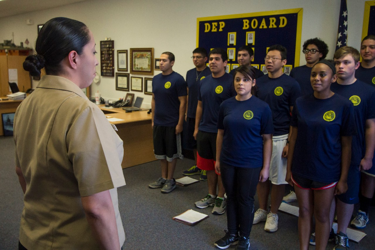 Aviation Boatswain's Mate (Equipment) 2nd Class Janel Banks, a recruiter assigned to Navy Recruiting District (NRD) Dallas, leads future Sailors in The Sailor's Creed during a weekly Delayed Entry Program meeting.