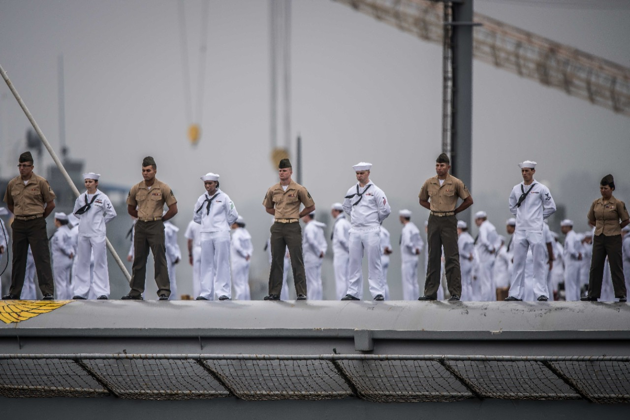 Sailors and Marines aboard the aircraft carrier USS Nimitz (CVN-68) man the rails and give passing honors to the USS Midway Museum.