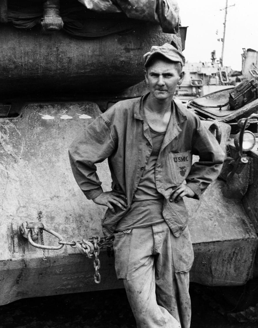 U.S. Marine stands by the front of a M-46 tank, which has three North Korean tank kills to its credit, on the Inchon waterfront