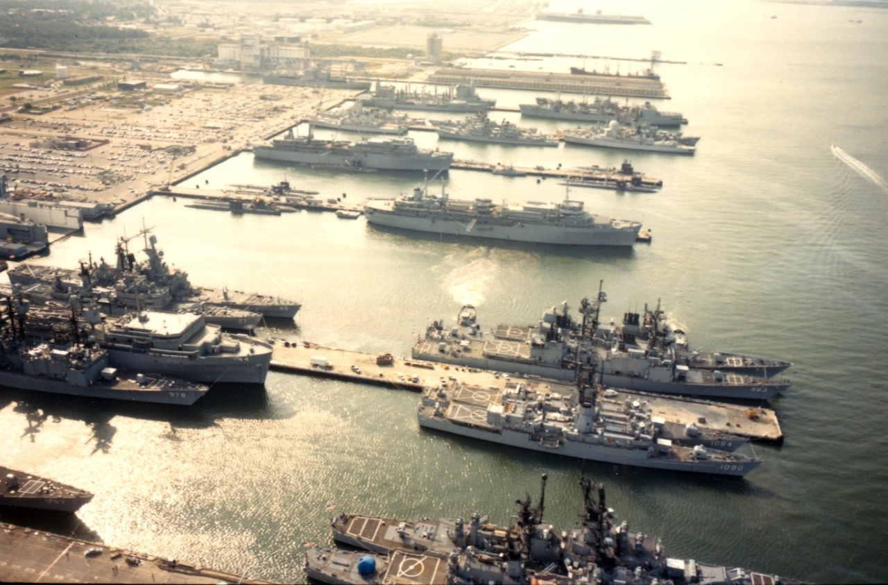 Naval Station, Norfolk, VA - an aerial view of the destroyer and submarine piers (Nos. 22 and 23) with various ships at anchor, including destroyers, frigates, cruisers, destroyers and submarine tenders and submarines. October 1984.
